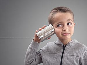 Boy on tin can phone pretending to hear