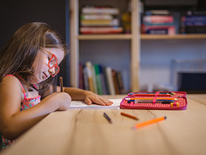 Little girl writing with colored pencils at the desk